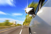 Car on the road with motion blur and sunlight in the mirror — Stock Photo