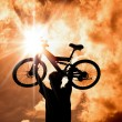 The Silhouette of mountain biker raised bicycle with sunset and cloud background — Stockfoto