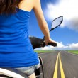 Slim woman riding scooter with high speed on the road — Stock Photo #10663941