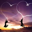 Young couple jumping and drawing connected hearts by flashlight — Stock Photo