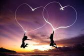 Jong koppel springen en verbonden harten tekenen door flitslicht — Stockfoto