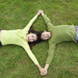 Happy  asian couple lying on the grass — ストック写真