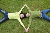 Happy asian couple lying on the grass — Stock Photo