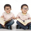 Happy kids with big book wearing black glasses — Stock Photo #8096182