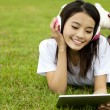 Happy girl using tablet pc on the grass — Foto Stock