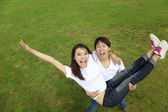 Happy asian couple on the grass — Stock Photo
