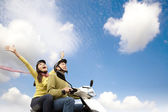 Happy young couple having fun on a scooter — Stock Photo