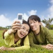 Asian couple taking photo by smart mobile phone — Stock Photo