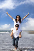 Happy couple running in the water at the beach — Stock Photo