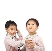 聴診器による健診と 2 人の子供 — ストック写真