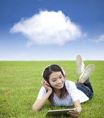 Happy girl using touch pad computer with headphone on the meadow — Stock Photo