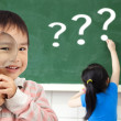 Happy kids with drawing question mark in the classroom — Stock Photo