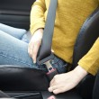Woman hand fastening a seat belt in the car - Stock Photo