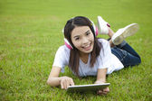 Young woman using tablet pc on the grass — Stok fotoğraf