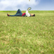 Young man lying on the grass fie - Stock Photo
