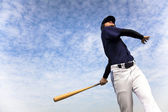 Baseball player taking a swing with cloud background — Stock Photo