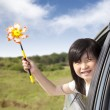 Happy little girl holding windmill in the car — Stock Photo