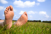 Relaxed foot on grass with cloud background — Stock Photo