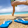 Man running on the beach and slipper - Stock Photo