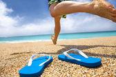 Człowiek działa na plaży i slipper — Zdjęcie stockowe