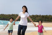 Asian mother with children walking on the beach — Стоковое фото