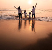 Happy family holding hands on beach and watching the sunset — Stok fotoğraf