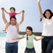 Happy asian family jumping on the beach — ストック写真