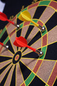 Dartboard with yellow and red magnetic darts — Stock Photo