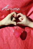 Un cuore con le dita e sfondo con scritta amore — Stock Photo