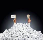Help me! Person under crumpled pile of papers with a help sign a — Stock Photo