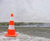 Cône de circulation typique d'orange et blanc devant le mur blanc — Photo