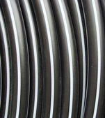 Plastic black rolled up hose or cable — Stock Photo
