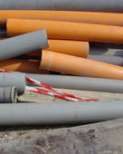 Industrial orange and gray pipes laying on pavement — Stock Photo