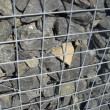Detail of fence wall made of stones in metal cage — Stockfoto