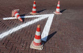 Arrow with typical orange and white traffic cone on pavement — Stock Photo