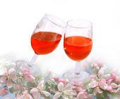 Wine glasses among spring flowers — Stock Photo