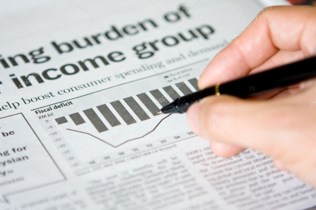 Hand holding pen on a financial newspaper. — Stock Photo #9458130