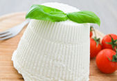Ricotta cheese with basil leaves. — Stock fotografie
