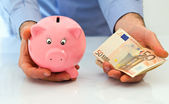 Man with piggybank and stack of euro banknotes. — Stock Photo