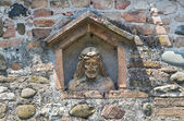 Stone Christ in a wall niche. — Stock Photo
