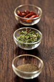 Spices and herbs in glass bowls. — Photo