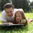 Fatherr and little girl reading book together — Stock Photo