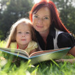 Stock Photo: Mother and little girl reading book