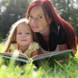 Mother and baby girl reading book — Stock Photo #9626139