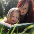 Mother and baby girl reading book — Stock Photo #9626157