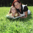 Mother and little girl reading book together — Stock Photo #9626173