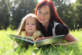 Mother and little girl reading book — Stock Photo