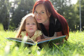 Mother and baby girl reading book — Stock Photo