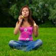 Girl blowing soap bubbles — Stock Photo