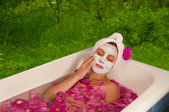 Beautiful woman enjoying floral bath — Stock Photo